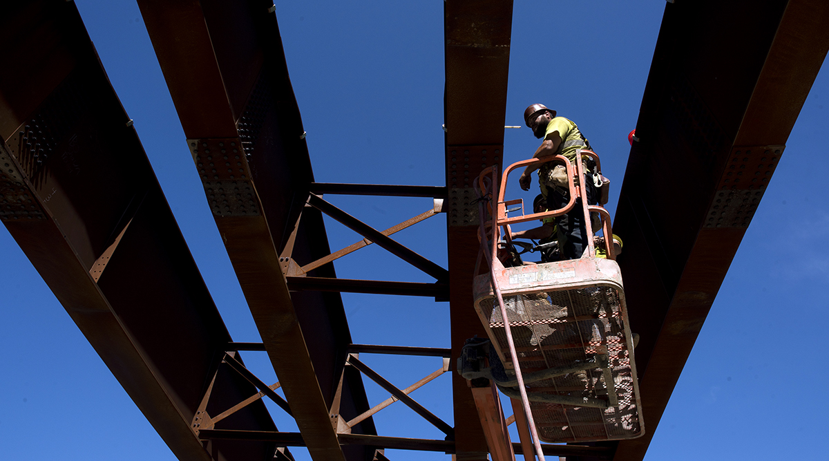 A contractor stands on a cherry picker to work on steel beams during highway construction between U.S. Route 23 and U.S. Route 52 near Portsmouth, Ohio.