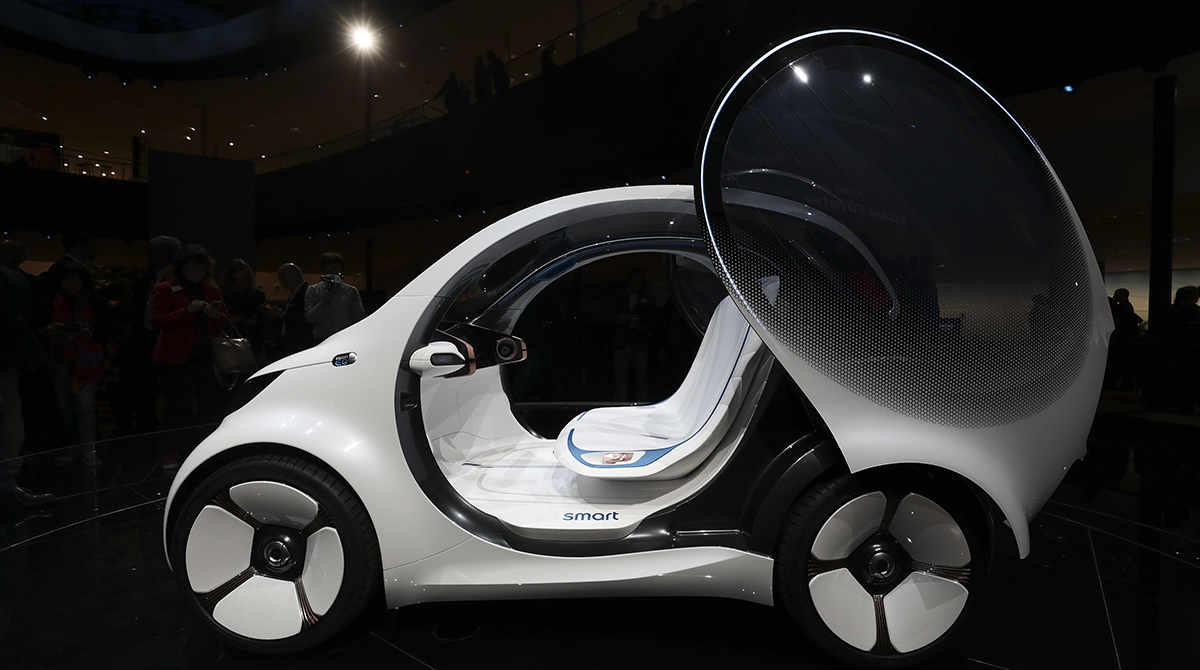 A door sits open on a Daimler Smart Vision EQ fortwo electric autonomous self-driving concept automobile.