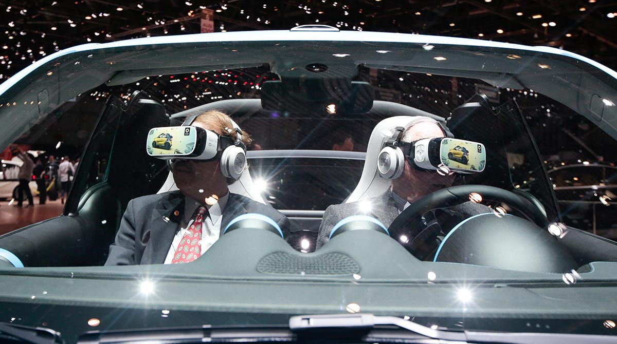 Attendees try a virtual reality (VR) experience in Smart Brabus concept vehicle, manufactured by Daimler AG, on the second day of the 86th Geneva International Motor Show in Geneva, Switzerland on Wednesday, March 2, 2016.