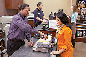 Customers return packages at a FedEx store