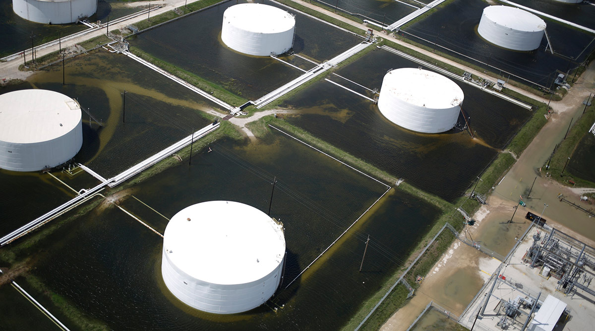 Rainwater surrounds oil refinery storage tanks