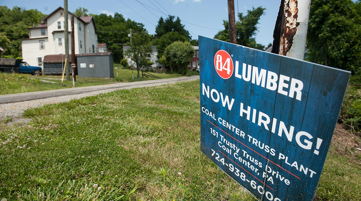"""A """"Now Hiring"""" sign stands outside the 84 Lumber Co. California Truss Plant in Coal Center, Pennsylvania, U.S., on Friday, June 9, 2017. One of the nation's largest building-supply chains, 84 Lumber Co., spends millions on ads to drive home its message th"""