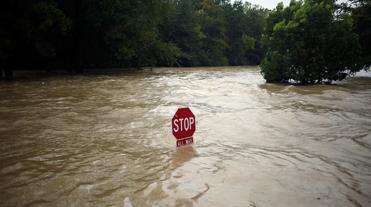 """A """"Stop"""" sign stands in floodwaters due to Hurricane Harvey in Spring, Texas, U.S., on Monday, Aug. 28, 2017.;"""