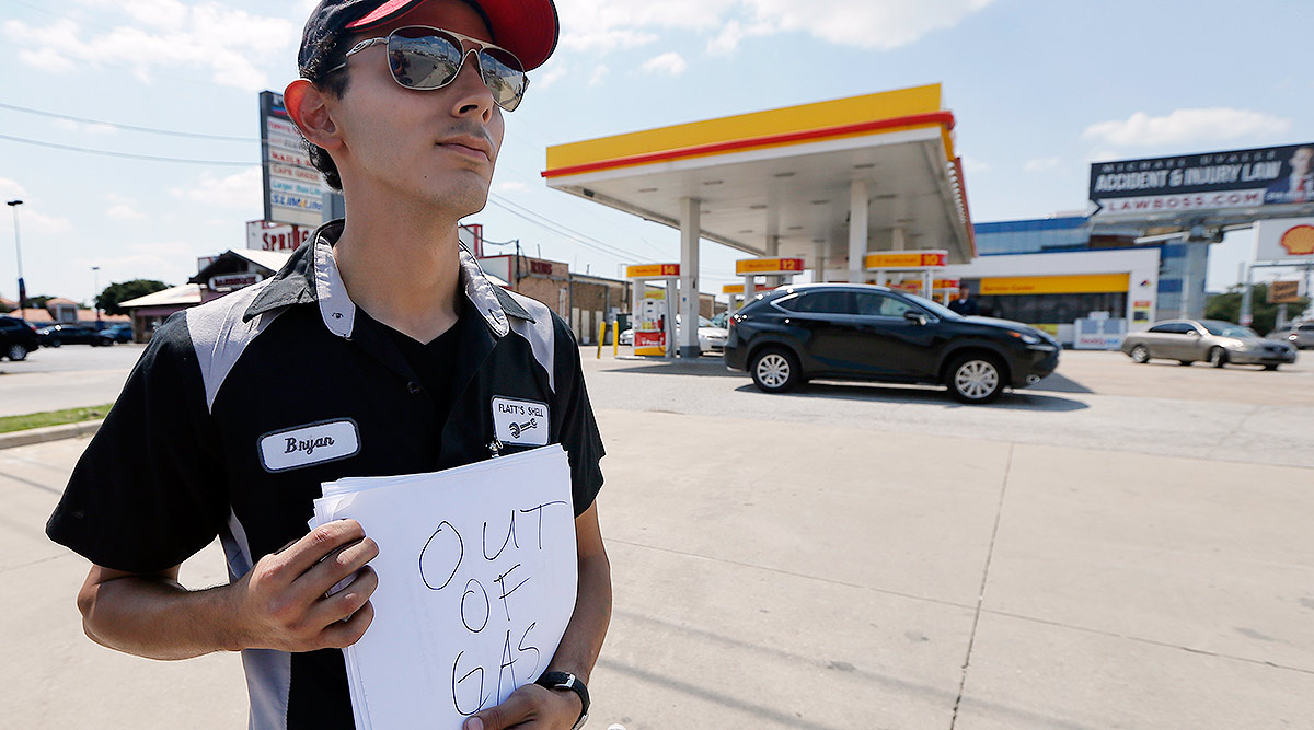 """Gas station employee holds """"out of gas"""" sign"""