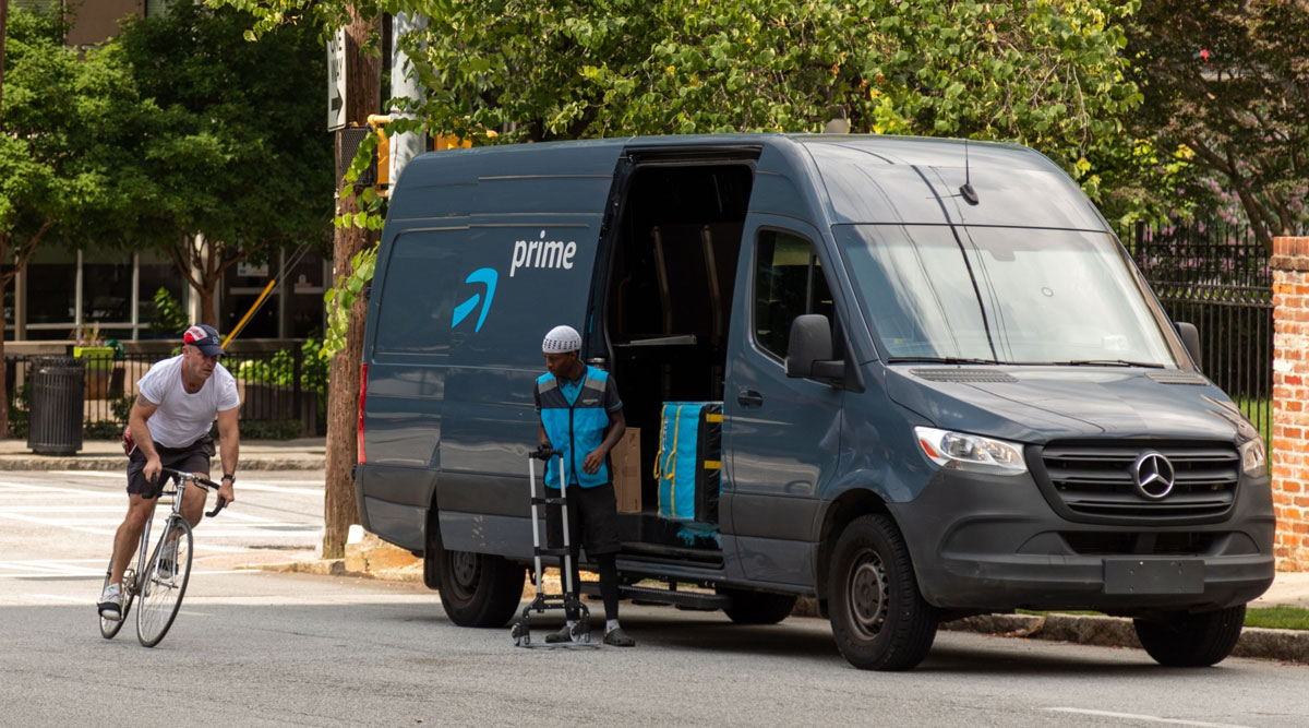 A pedestrian rides a bike past an Amazon Prime delivery van in Atlanta on July 21.