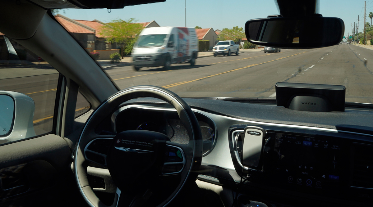 A Waymo minivan moves along a city street with an empty driver's seat in Chandler, Ariz. (Ross D. Franklin/Associated Press)