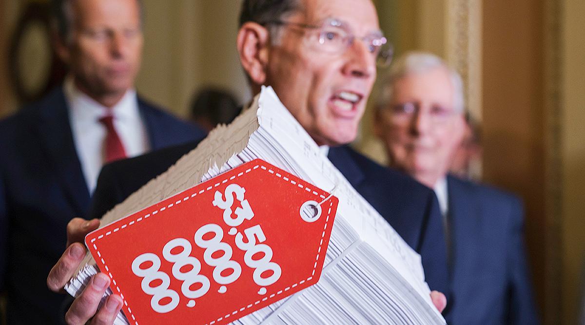 "Sen. John Barrasso hoists a copy of the Democrats' $3.5 trillion ""Build Back Better"" package"