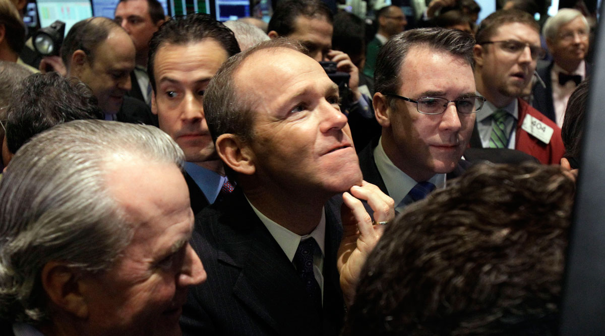 In this January 2011 file photo, Nielsen Company CEO David Calhoun, center, watches progress as he waits for the company's IPO to begin trading, on the floor of the New York Stock Exchange.