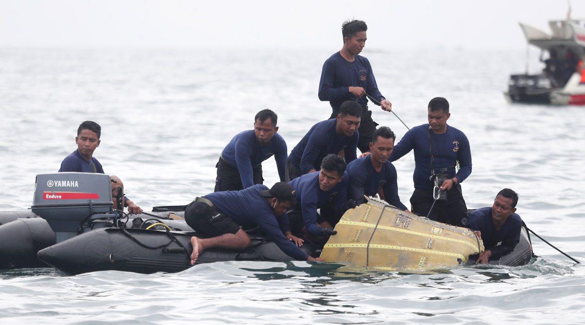 Indonesian Navy divers pull out airplane pieces during a search operation for the Sriwijaya Air passenger plane.