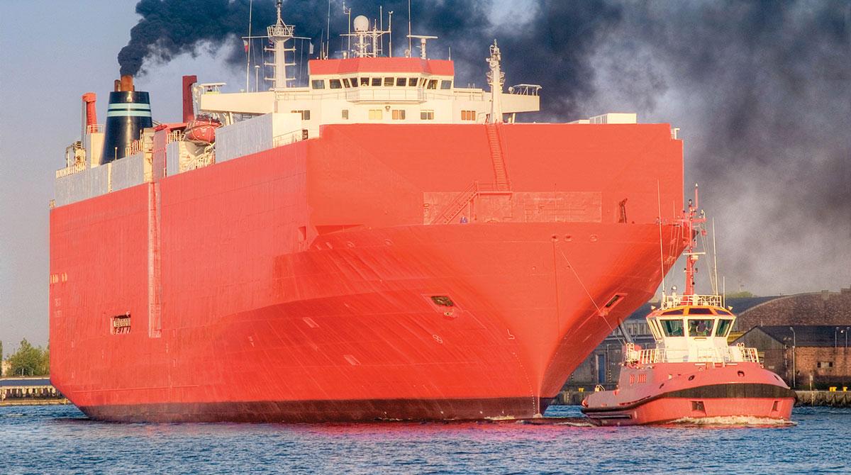 A cargo ship spews black smoke