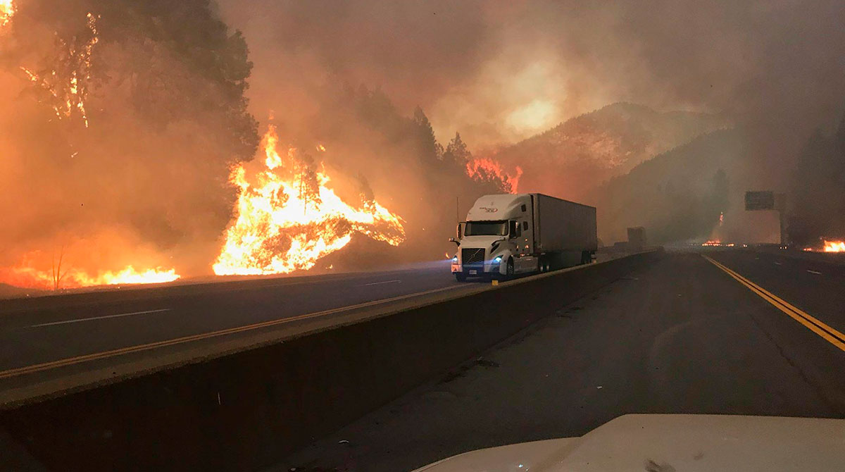 A truck drives next to the Delta Fire burning on I-5