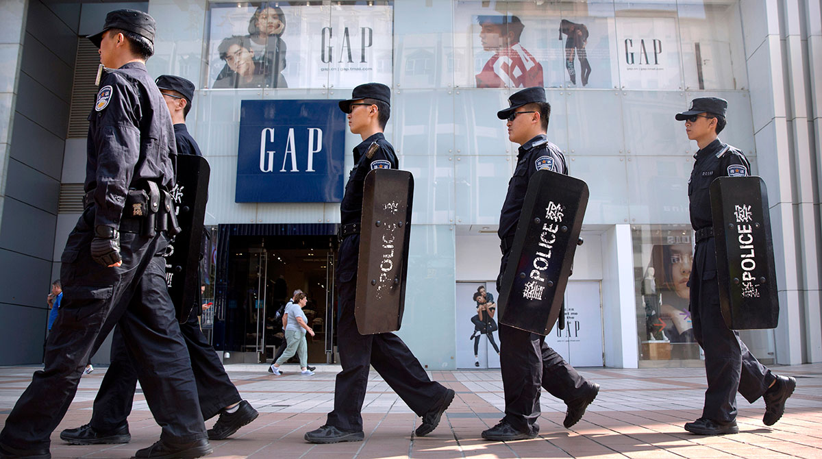 Beijing police patrol in front of a Gap store