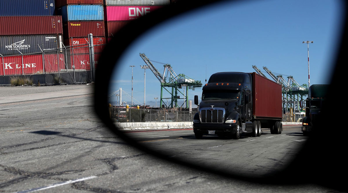 A truck loaded with a shipping container drives through the Port of Oakland in September 2019.