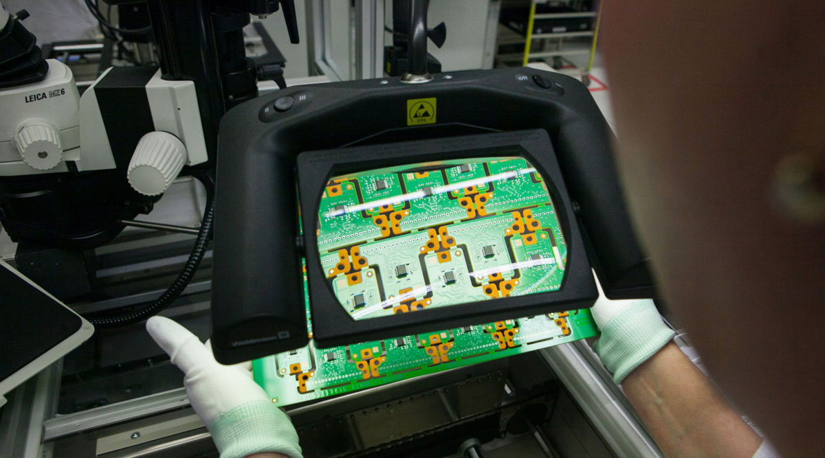 A circuit board is inspected under a magnifying lens inside Continental AG's factory in Germany.