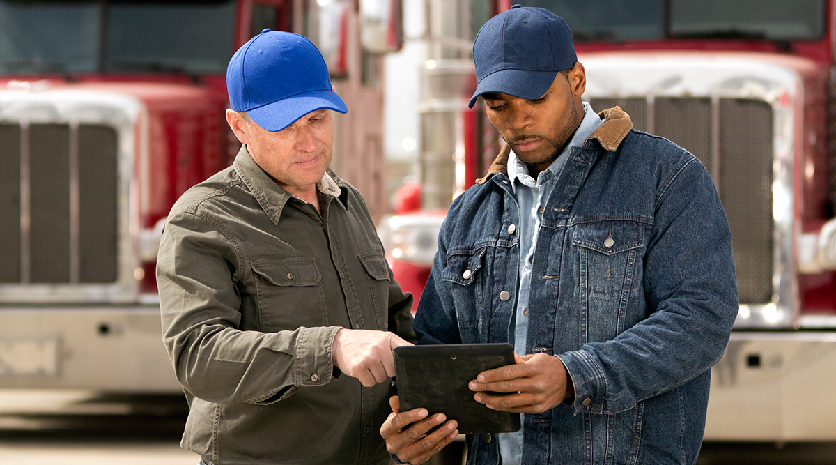 Two truck drivers having a meeting using a tablet computer.
