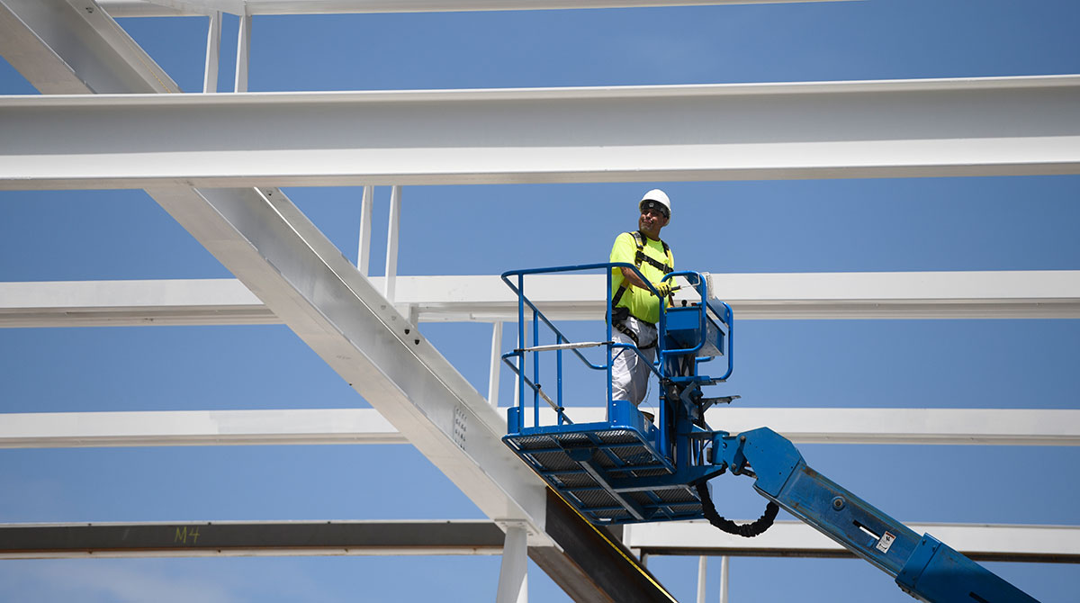 A construction worker lowers himself on a forklift at a construction site in Chicago.