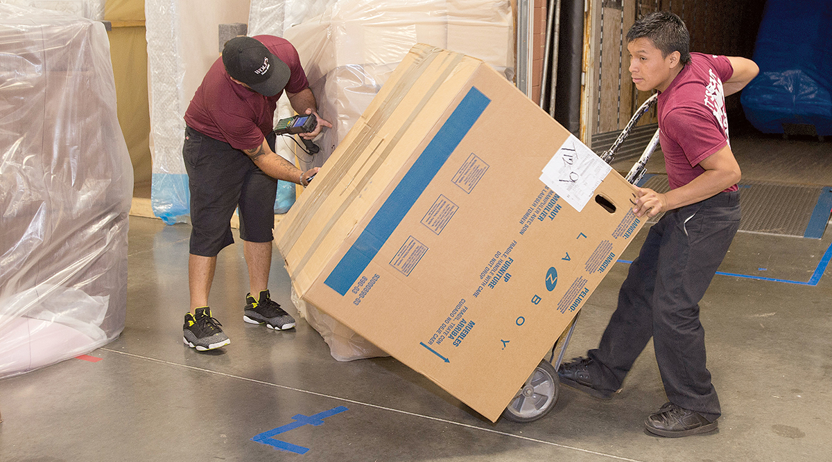 Workers for Cory 1st Choice Home Delivery unload furniture.