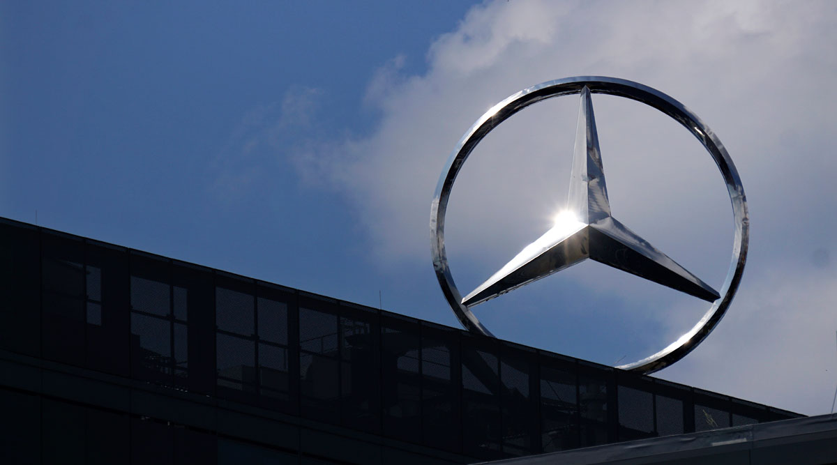 Sunlight reflects in a Mercedes Benz logo on top of an office building in Berlin, Germany.