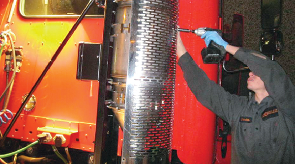 A technician installs a retrofit diesel particulate filter on a truck at the Ironman Renewal facility in San Leandro, Calif.