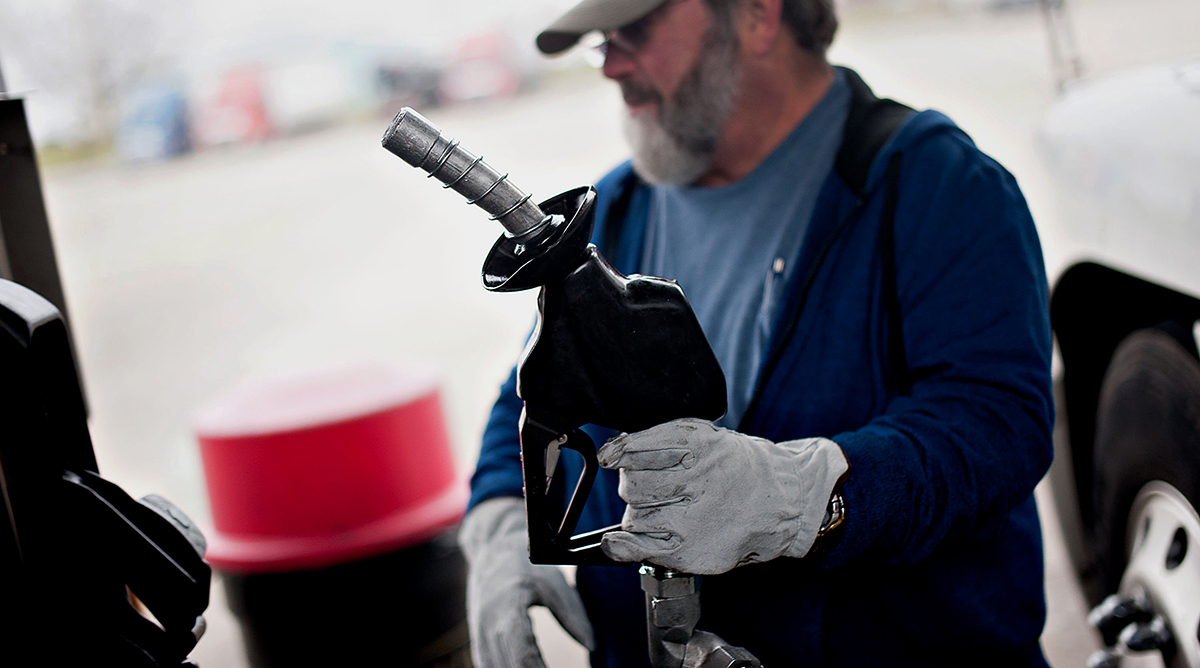 A truck driver pumps diesel