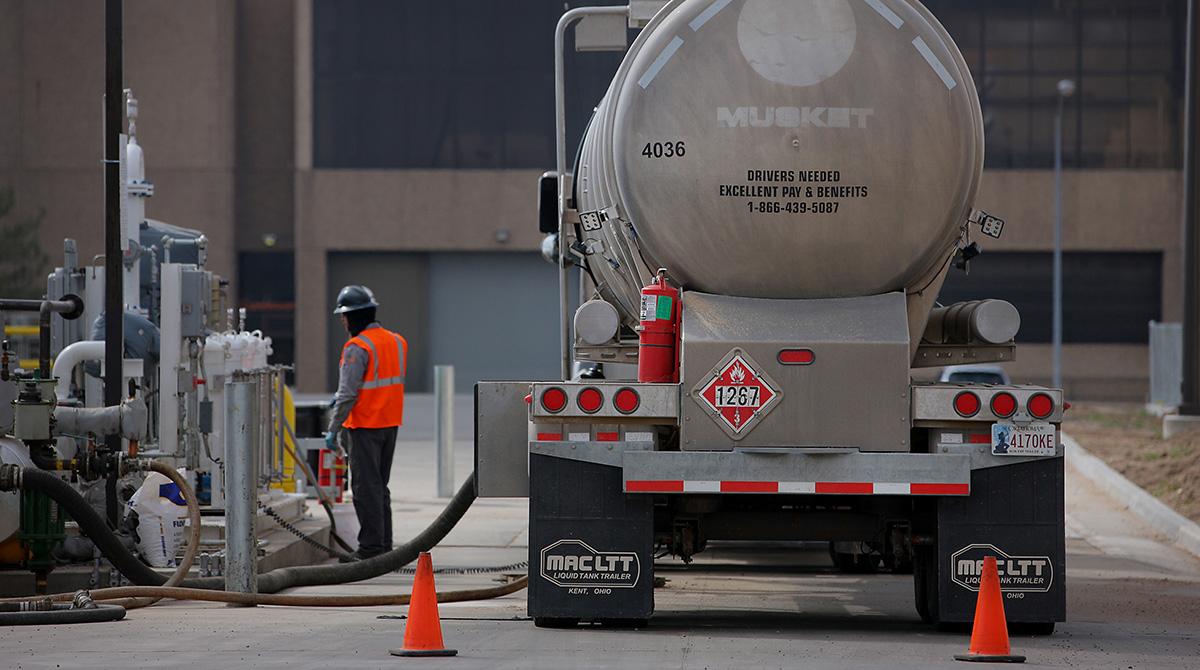 A tanker fills underground storage tanks with fuel