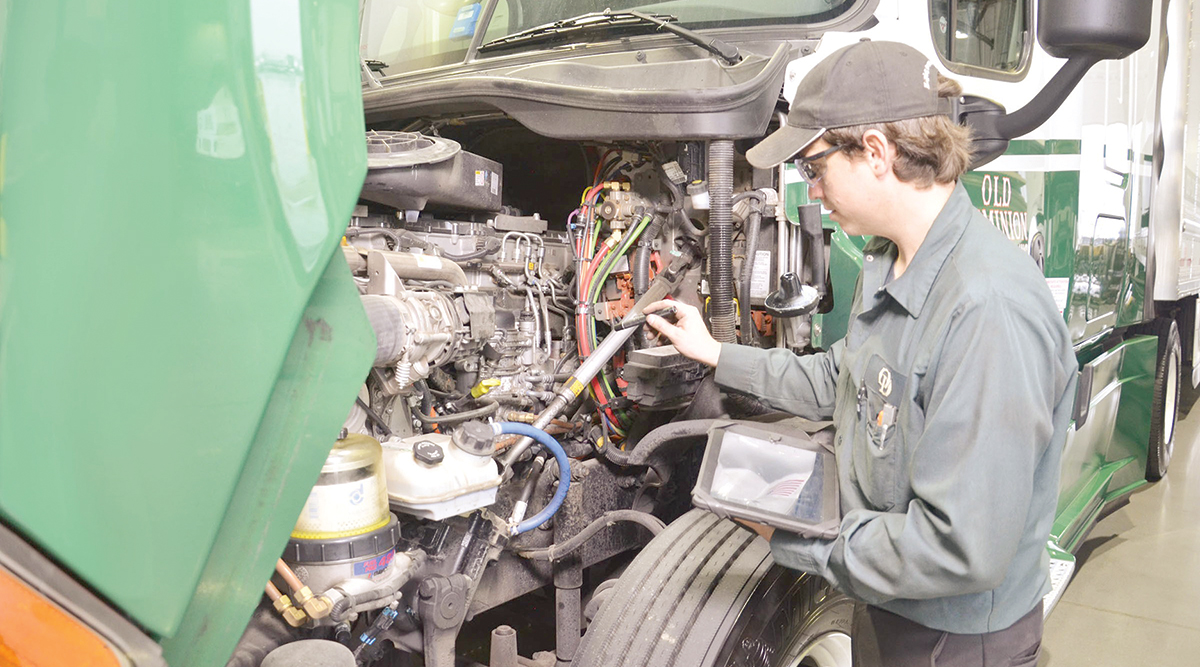 A technician checks diagnostics on a tractor's engine