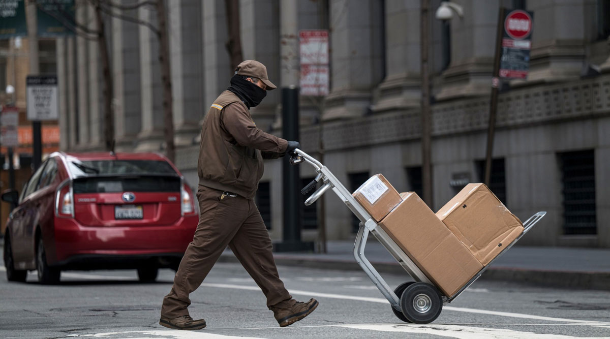 A UPS delivery driver pushes a hand truck loaded with packages in San Francisco.