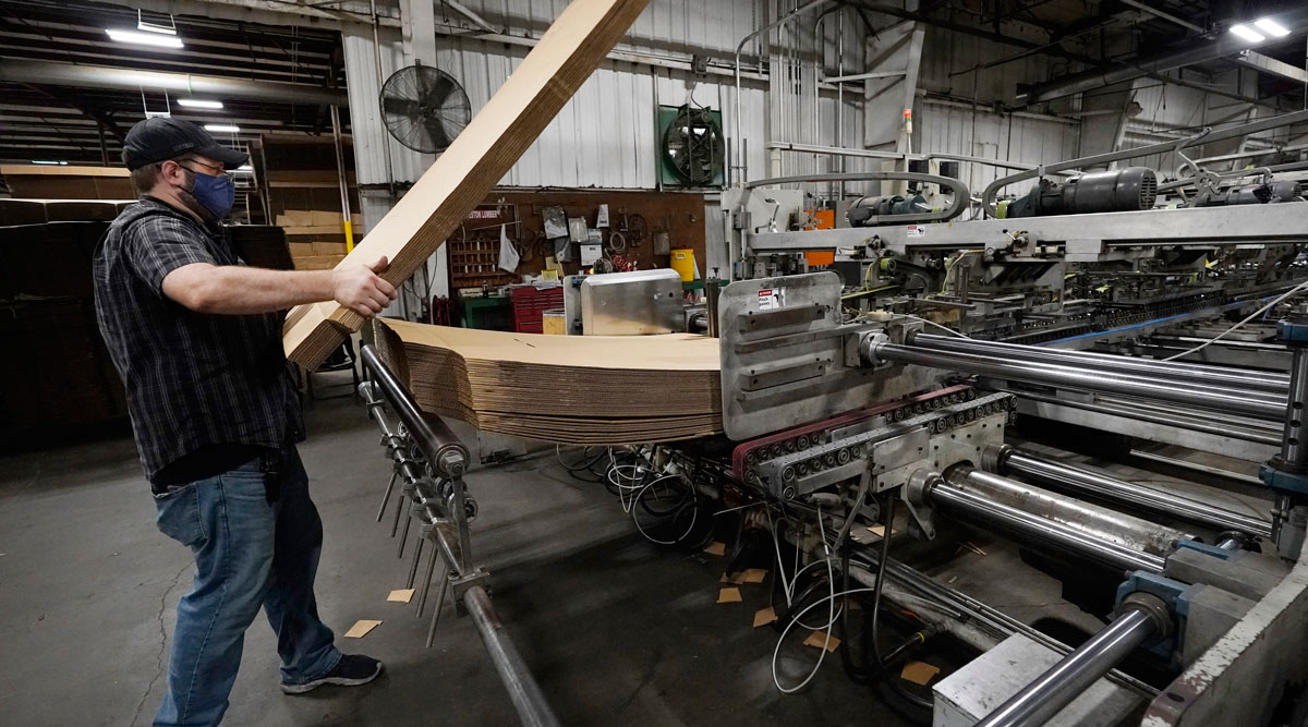 A supervisor at a packaging company in Jackson, Miss., loads up a finishing machine. (Rogelio V. Solis/Associated Press)