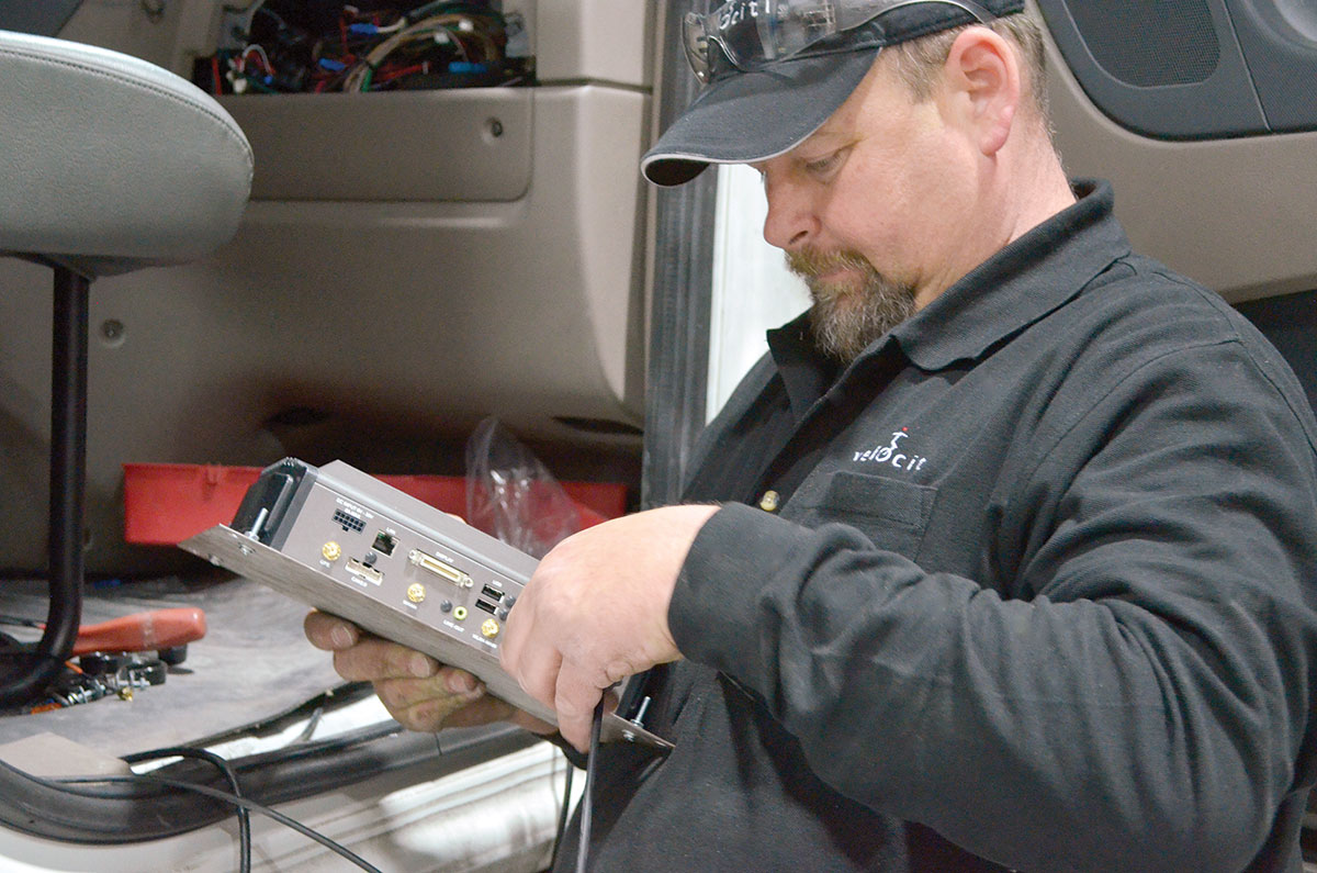 A Velociti technician works on in-cab technology