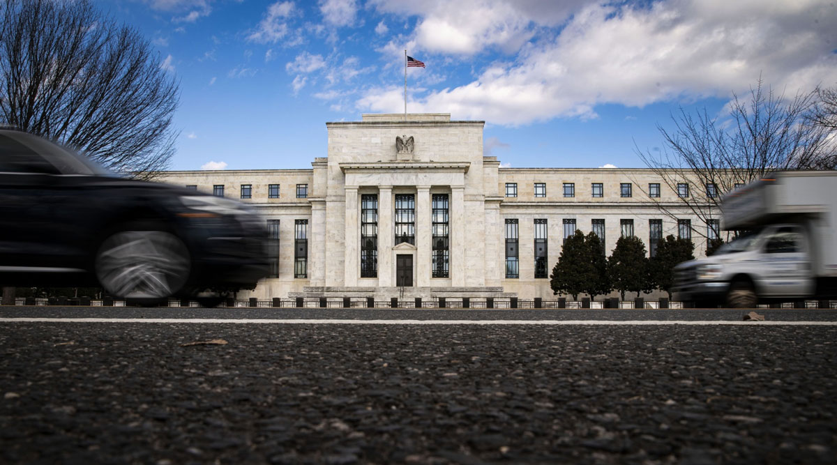 Vehicles pass in front of the Federal Reserve building in Washington. (Al Drago/Bloomberg News)