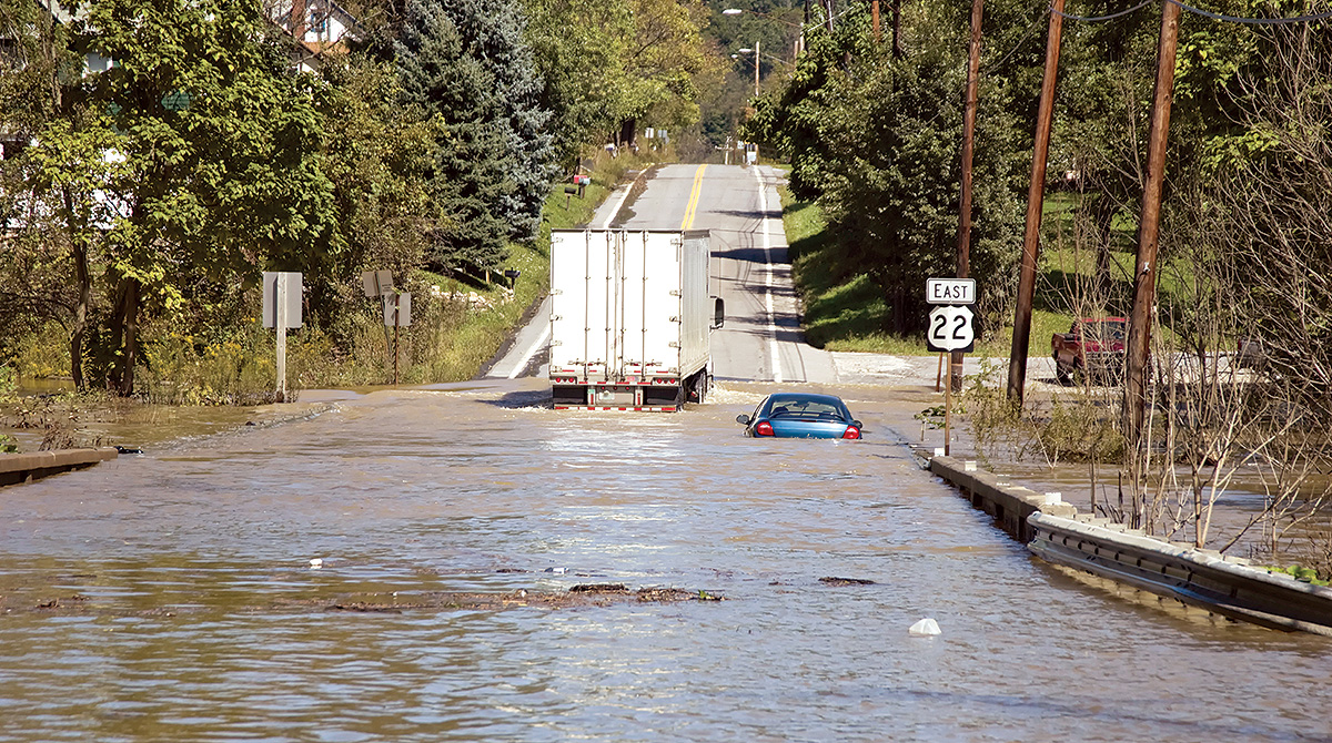 Vehicles try to cross flooded road