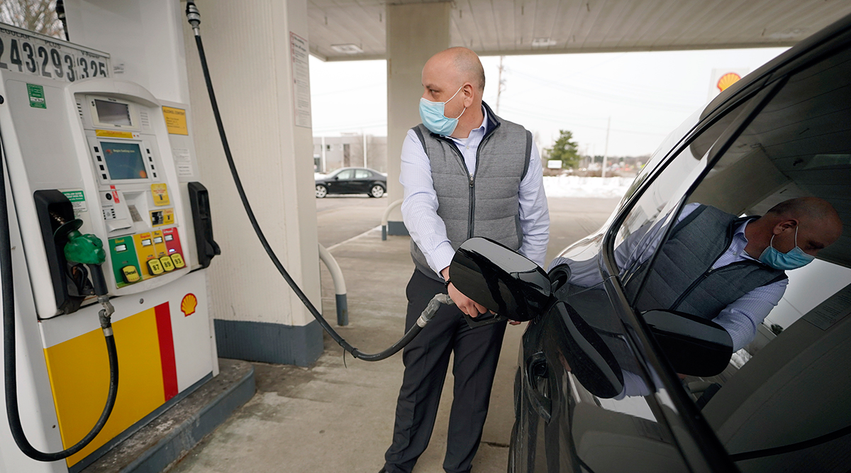 A man pumps gas at a Shell station in Massachusetts