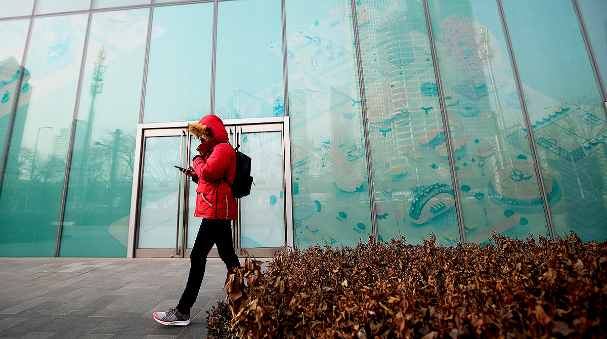 Man walking by empty storefront in Beijing's Central Business District