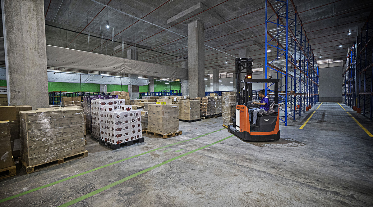 Warehouse inventory is moved with a forklift.