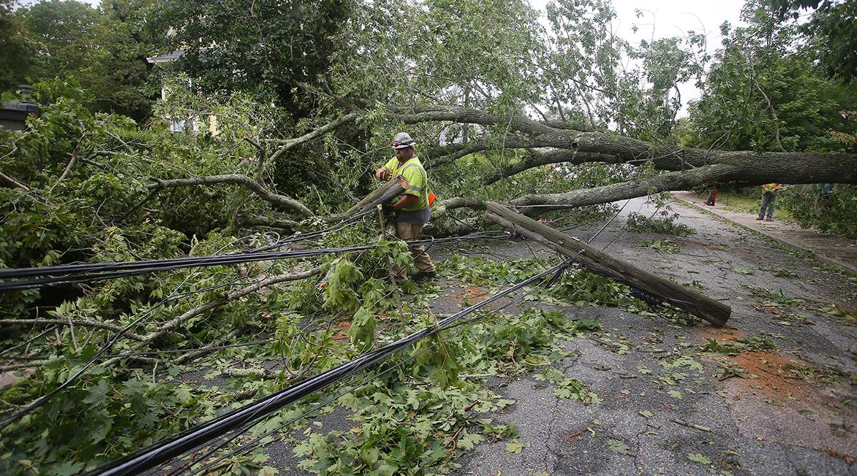 A crewman removes a snapped electrical pole in Narragansett, R.I.