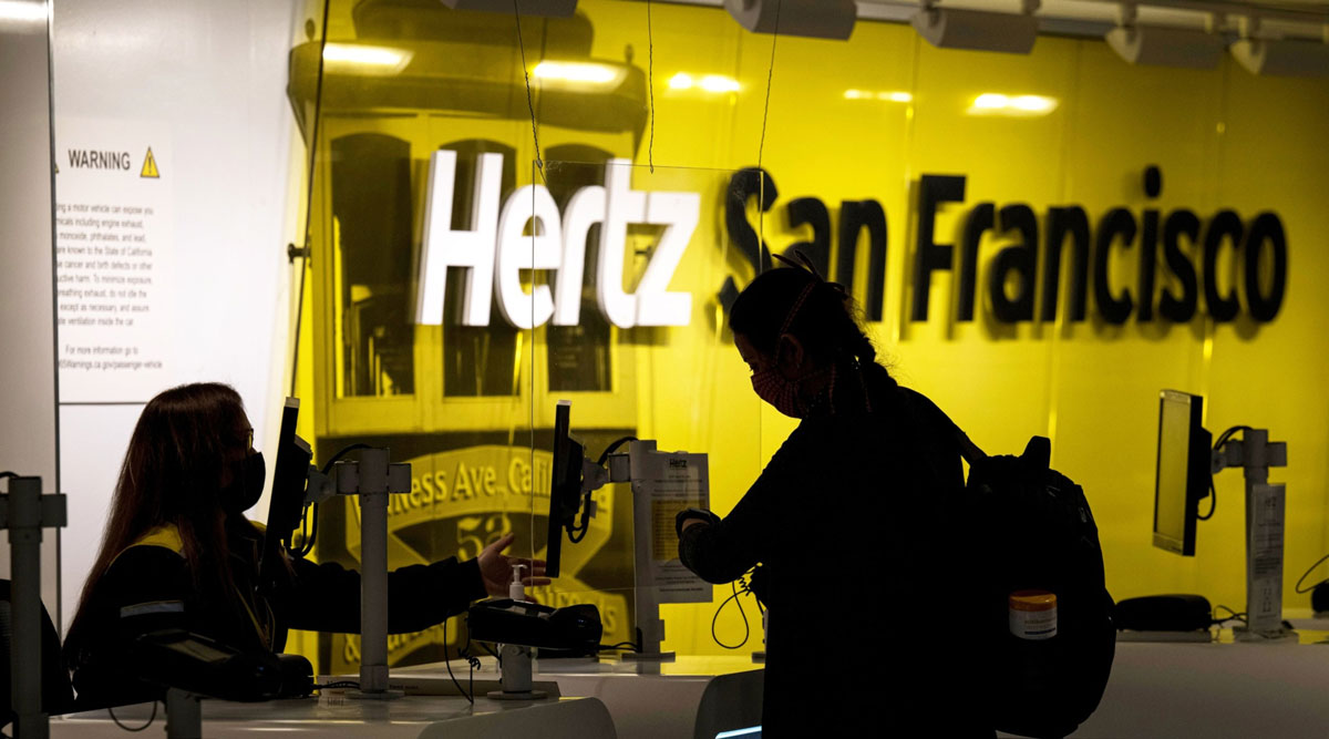 Employee wears mask while assisting a customer at a Hertz counter in San Francisco