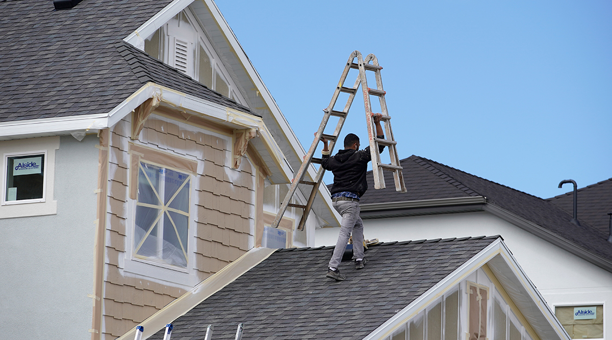 Man working on roof of house