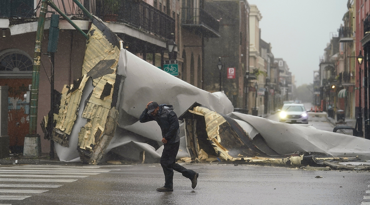 A man in New Orleans' French Quarter passes by a section of a roof blown off by Hurricane Ida