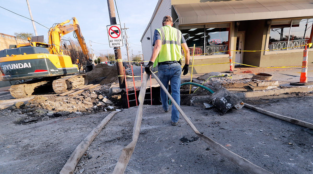 Workers fix a sewer main below the sidewalk in New Orleans