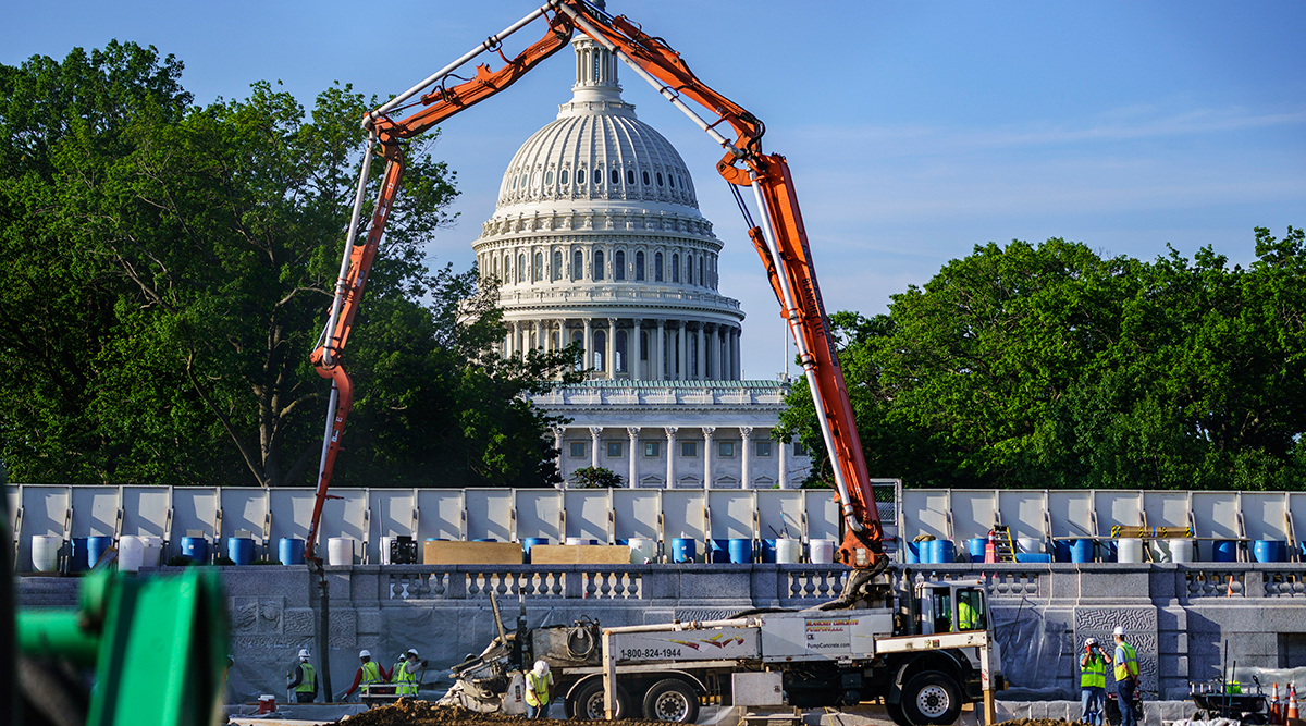 A concrete pump frames the Capitol Dome during renovations and repairs