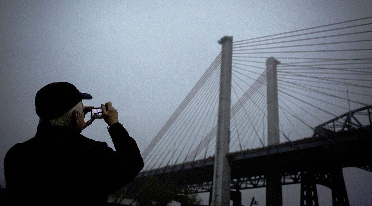 Man in front of bridge