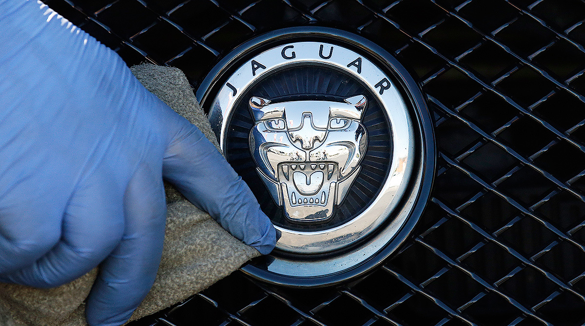 Hand polishing Jaguar logo
