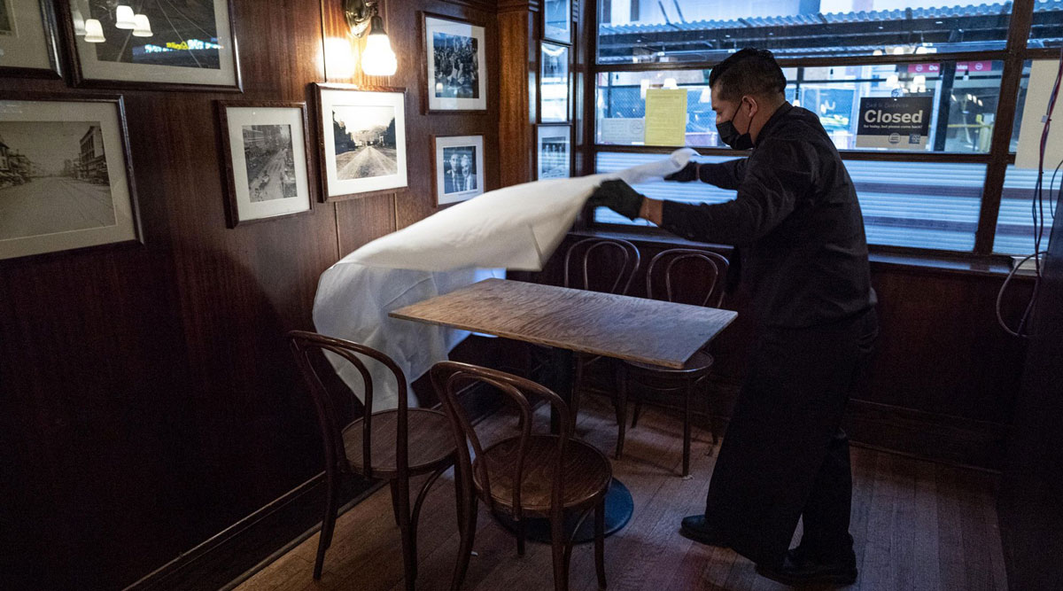 A workers puts down a table cloth at a restaurant in San Francisco. (David Paul Morris/Bloomberg News)