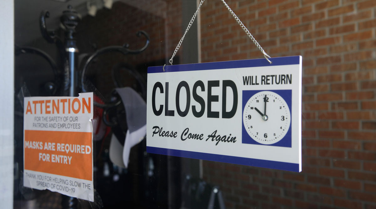 A closed sign hangs in the window of a barber shop in Burbank, Calif., on July 18.