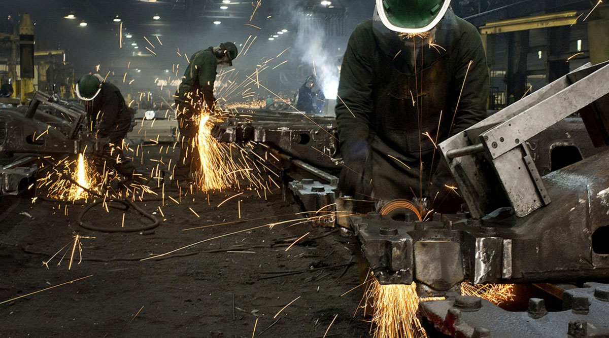 Workers use grinders to smooth the welded joints for railroad suspension parts.