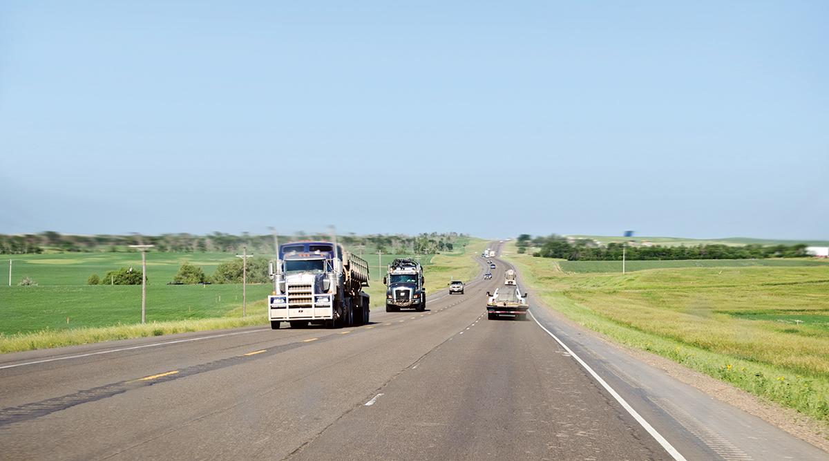 Vehicles travel on road in North Dakota