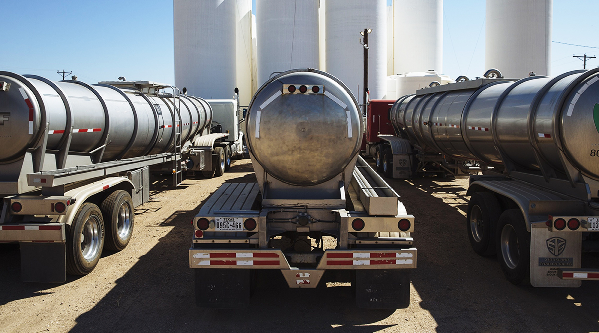 Tanker trucks sit in front of storage silos in Sunray, Texas