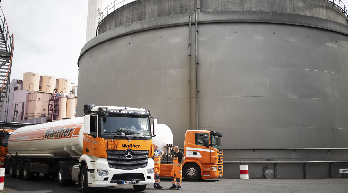 Oil tanker trucks sit parked beside storage silos in Germany in June 2019.
