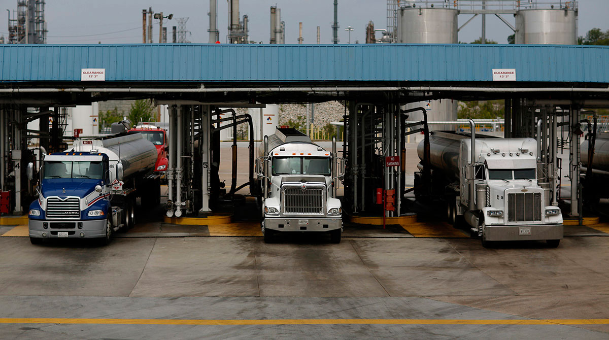Trucks transporting oil exit a Valero facility
