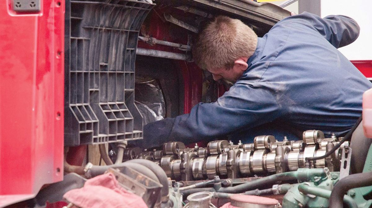 A technician repairs a Class 8 truck